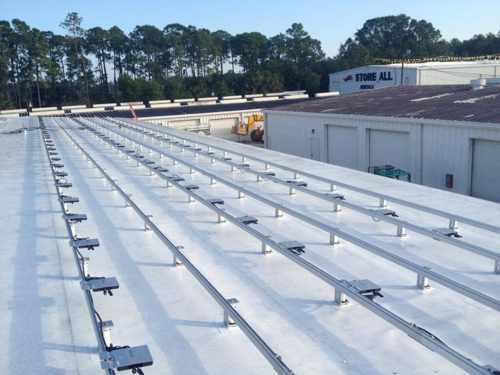 Microinverters mounted to solar rails, lined up and ready for solar panels to be installed.